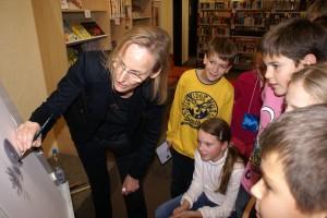 Das Foto zeigt die Künstlerin Gisela Kalow mit Mitgliedern des Leseclubs am Friedrich-Spee-Gymnasium mit ihrem lesenden Phantasievogel in der Bilderbuchwerkstatt.