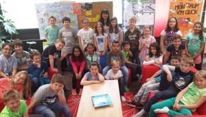 Das Foto zeigt die Autorin Uschi Flacke mit den Kulturbotschaftern des Leseclubs vom Friedrich-Spee-Gymnasium und den Schülerinnen und Schülern der 3. Jahrgangsstufe der Grundschule Ehrang.