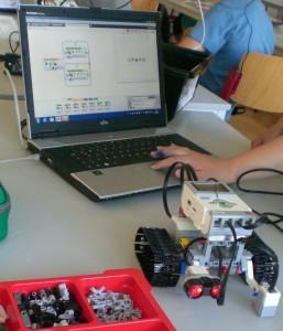 Lego Roboter mit Bausteinen und Programmieroberfläche.