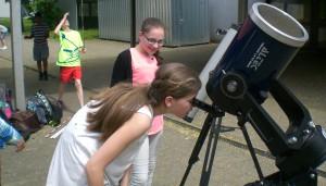 Schülerinnen beobachten, wie sich Merkur vor die Sonne schiebt.