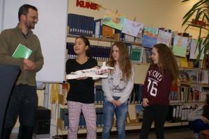Alice, Emilie und Lisa zeigen Autor Stefan Gemmel ihre Bastelarbeit.